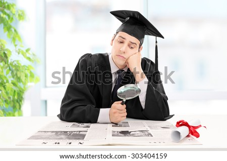 Student looking for a job in a newspaper at home with a magnifying glass - stock photo
