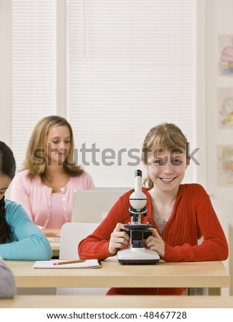Student looking into microscope in classroom - stock photo