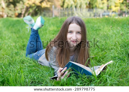 Student lying with book on the green grass