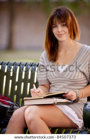 Student on bench taking notes in a journal - stock photo