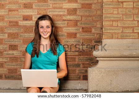 Student on campus with laptop - stock photo