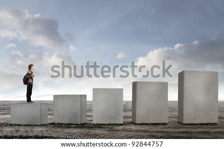 Student on the lowest of stone cubes in ascending order - stock photo