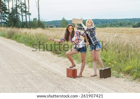 Student on vacations hitchhike on country road - stock photo