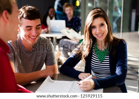 Student outside studying while smiling - stock photo