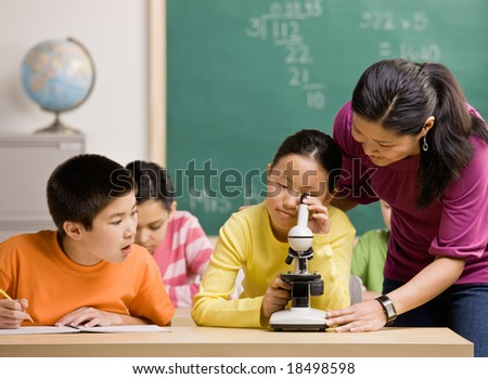 Student peering through microscope in science classroom - stock photo