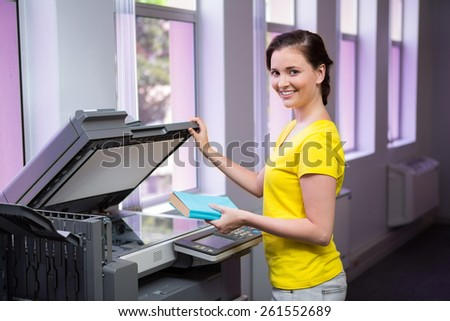Student photocopying her book in the library at the university - stock photo
