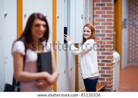 Student picking her binder in her locker while her friend is standing up - stock photo
