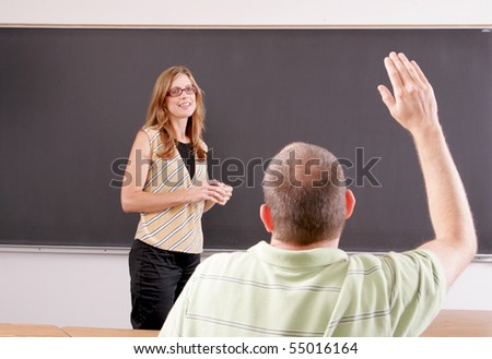 Student raising a hand with a question with the teacher looking - stock photo