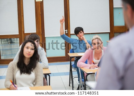 Student raising hand to ask question in college classroom - stock photo