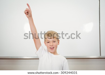 Student raising his hard in the classroom at the elementary school