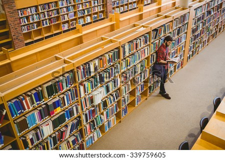 Student reading a book from shelf in library at the university - stock photo
