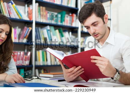 Student reading a book in a library - stock photo