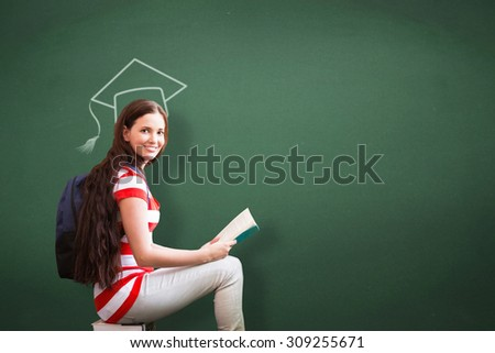 Student reading book in library against green - stock photo
