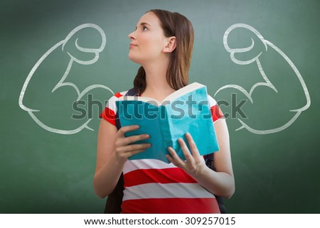 Student reading book in library against green chalkboard - stock photo