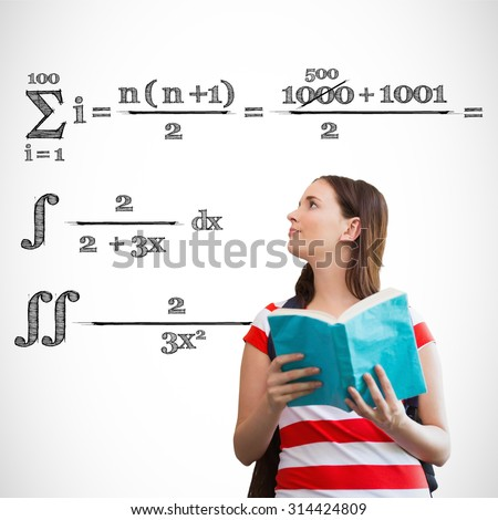 Student reading book in library against maths equation - stock photo