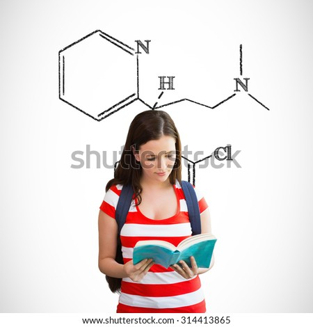 Student reading book in library against science formula - stock photo