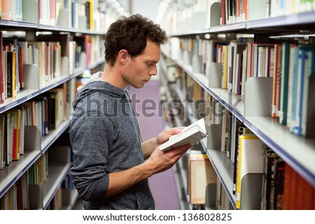 student reading book in library, university education - stock photo