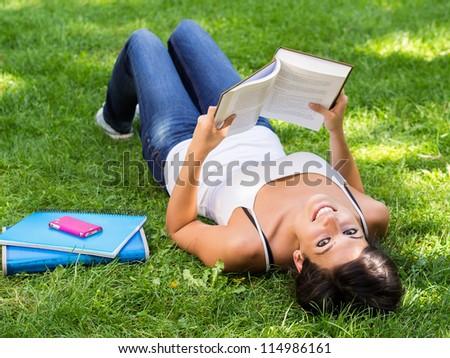 Student reading book in park. Happy caucasian girl studying outdoor in university campus. Caucasian brunette model. - stock photo