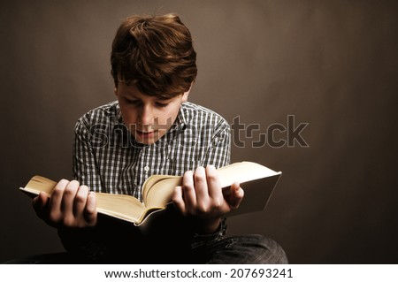 Student reading large book