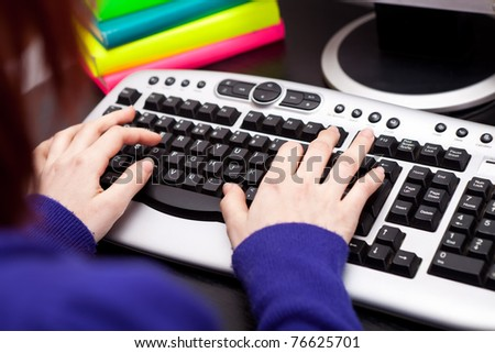 student's hands typing on keyboard - stock photo