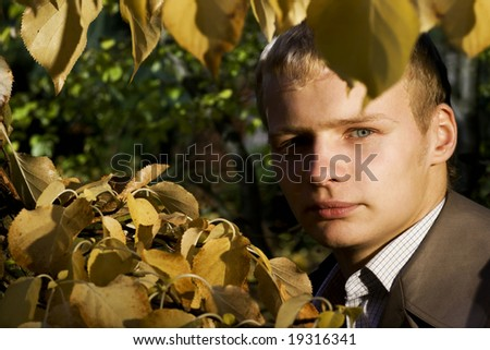 Student's portrait in leafes - stock photo