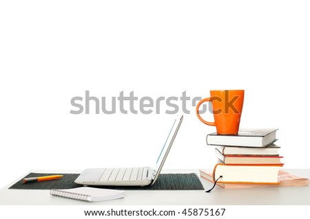 student's working and learning place with pile of books and laptop - stock photo