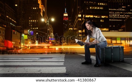 student seated on suitcase in a new york city street - stock photo