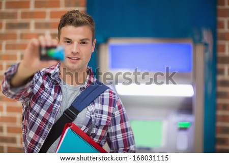 Student showing his card to camera at the atm in college - stock photo