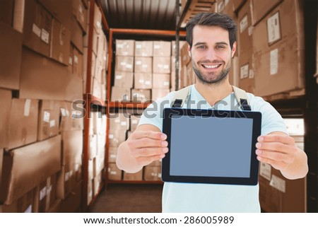 Student showing tablet against shelves with boxes in warehouse - stock photo