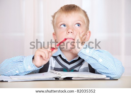 student sitting at a desk with a notebook and thinking how to do the job. boy with a thoughtful face - stock photo