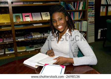 student sitting at a table reading a book in a library - stock photo
