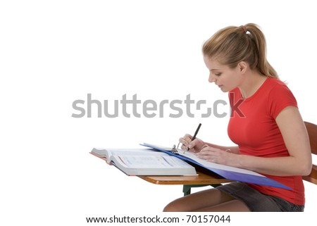 student sitting by the desk doing her math homework - stock photo