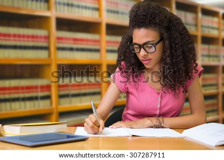 Student sitting in library writing against close up of a bookshelf