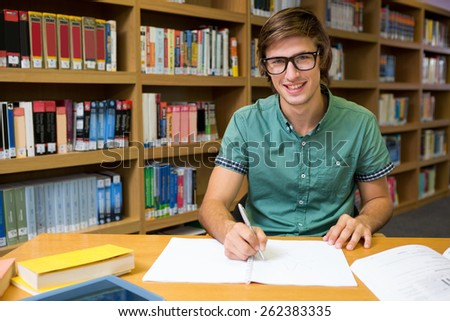 Student sitting in library writing at the university - stock photo
