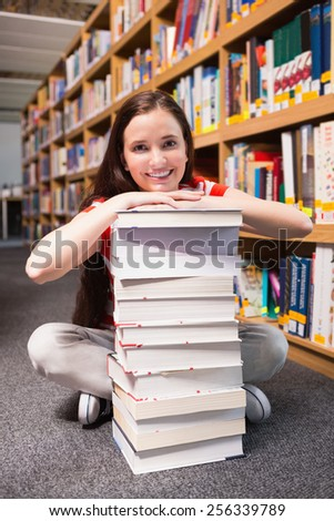Student sitting on floor in library at the university - stock photo