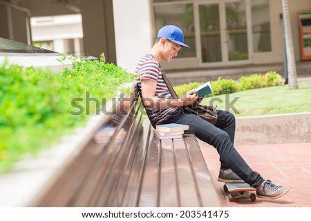 Student sitting on the bench and reading a book, side view - stock photo