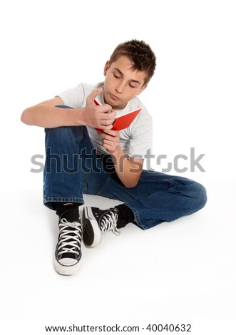 Student sitting on the floor reading - stock photo