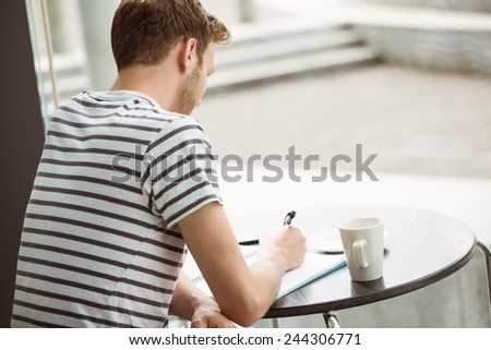 Student sitting with a hot drink and writing on notepad in cafe at the university - stock photo