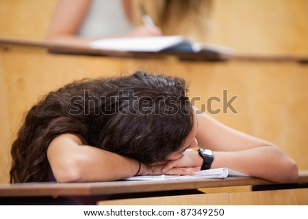 Student sleeping on her desk in an amphitheater - stock photo
