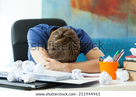 Student sleeping on the table before exam - stock photo