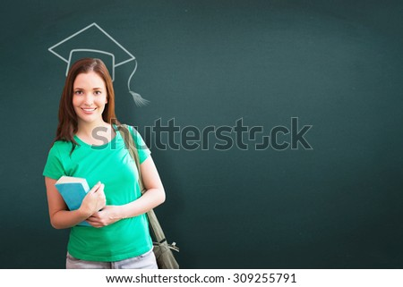Student smiling at camera in library against teal - stock photo