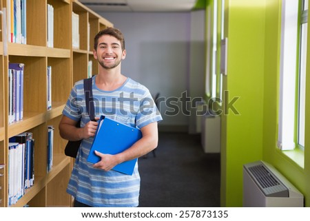Student smiling at camera in library at the university - stock photo