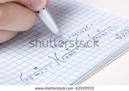 Student solving a math problem in a notebook. - stock photo