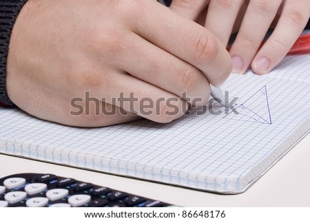 Student solving a math problem using a drawing of a triangle. - stock photo