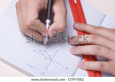 Student solving a math problem using a pen and a ruler. - stock photo