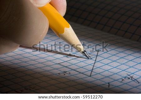 Student solving a math problem using a pencil. - stock photo