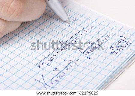 Student solving a mathematic problem in a notebook. - stock photo