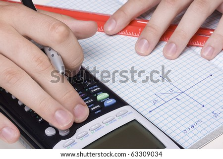 Student solving a trigonometry problem using a calculator. - stock photo