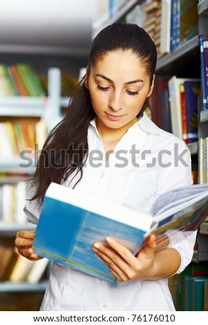 Student standing in the library and reading a book - stock photo