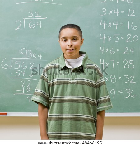 Student standing near blackboard - stock photo